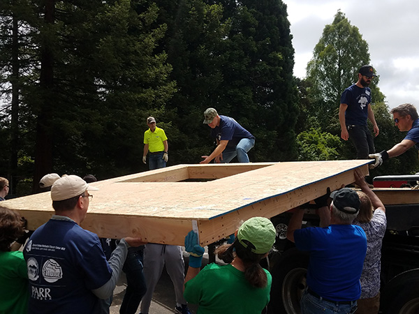Habitat for Humanity Volunteers working together to carry a wooden wall
