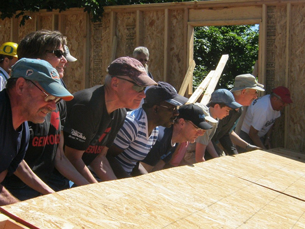 Habitat for Humanity volunteers working together to lift up a wall