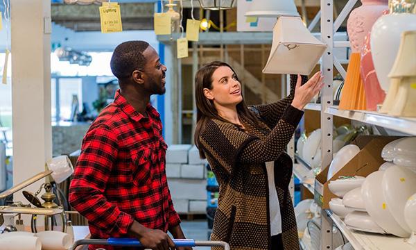 Woman helping man choose lamp shades at a ReStore