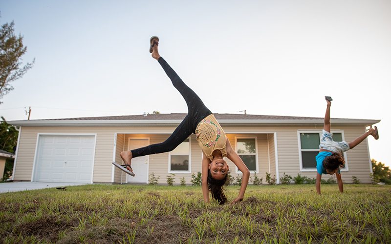 two girls doing cartwheels in front of home
